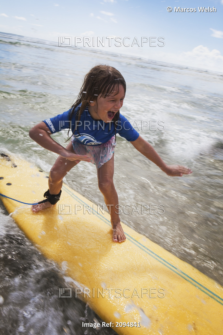 A young girl on a yellow surfboard;Gold coast queensland australia