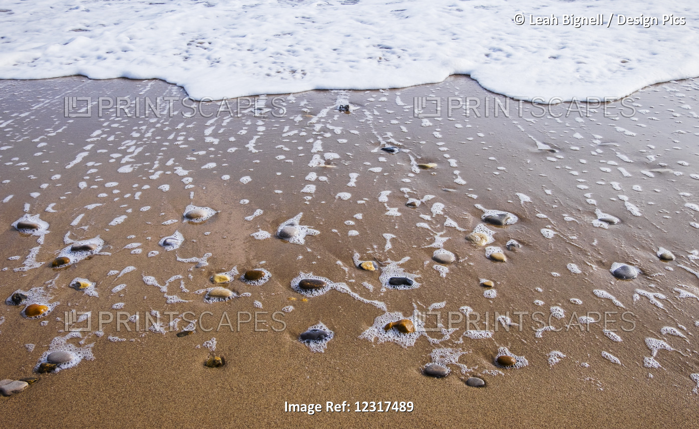 Sea Foam Trails From Beached Pebbles As The Tide Is Pulled Out; South Shields, ...